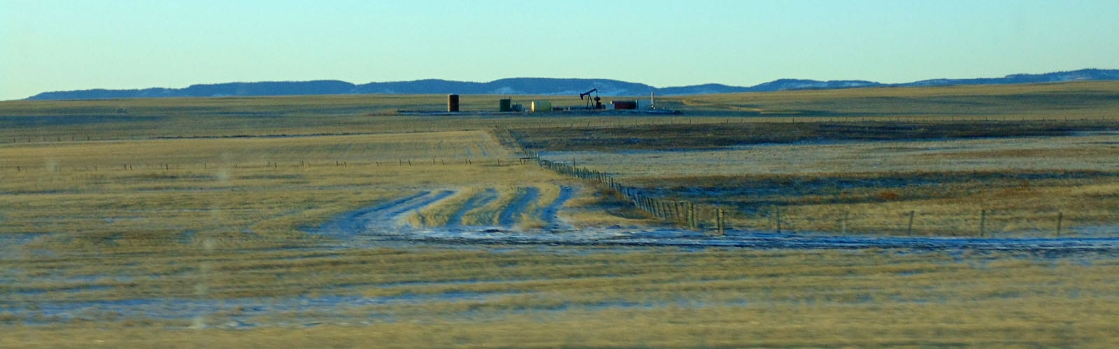 Alberta foothills with oilwell in foreground-sliver
